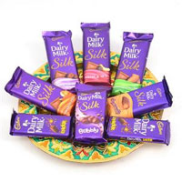 6 Dairy Milk Silk- Regular Chocolate, Orange Peel, Fruit & Nut, Caramello, Bubbly, Roasted Almond 2 Dairy Milk Crackle. <br> Accessories show are not part of the hamper.