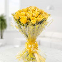 15 vibrant yellow roses surrounded by lemonium, wrapped in fancy cellophane paper , Flowers to Bangalore