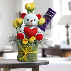 7 yellow roses with 1 pcs dairy milk chocolate and 6 inch white teddy in a glass vase