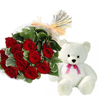 12 of the finest red roses are complemented by delicate gypsophila  with small teddy Bear
