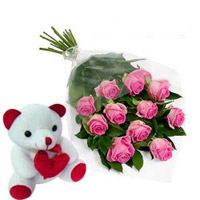 12 of the finest Pink roses are complemented by delicate gypsophila  with small teddy Bear
