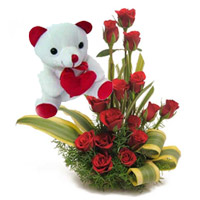 12 Red roses round basket with small teddy Bear