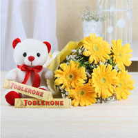10 Yellow Gerbera bunch Tissue Paper Wrapping Bunchs, 6 inch white teddy bear and 2 bars of Toblerone Chocolates (100 gms).