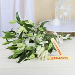 Send a romantic message of 'I love you to the moon and back' in a special way to your sweetheart Bunch of 10 White Lilies with 2 Toblerone Chocolate Bars