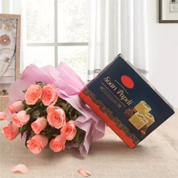 Give colorful surprise to your near and dear ones with this sweet gift hamper 10 Pink Roses Pink Packing Paper 500 grams Soan Papdi