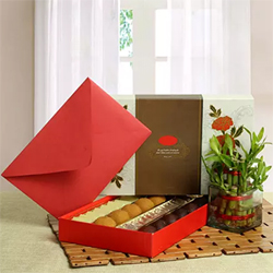 Assorted Kova sweets of 1 kilogram, two layer bamboo plant, and one greeting card are the ingredients of a great festive hamper