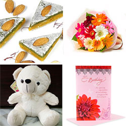 12 Multicolour Gerberas bunch +Barfi made of Kaju and Pista and decorated with silver foil.+Cream Teddy Cuddly teddy bear Height: 10 inch