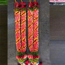 The varmala exchange ceremony is an important ritual in Indian marriage ceremony.  Yellow & Orange Roses Garland