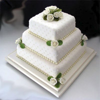 A beautiful square, stacked wedding cake with sugar roses and leaves. The upper tiers are on hidden cake 6 kg