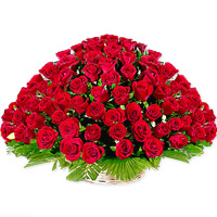 Collection of gorgeous 50 red roses bound together in a round bamboo basket, with a layer of green at the bottom.