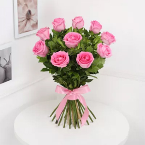 Bouquet of 12 attractive pink roses surrounded by seasonal fillers, wrapped in cellophane and tied with a ribbon