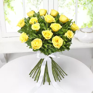 Collection of 12 vibrant yellow roses surrounded by lemonium, wrapped in fancy cellophane paper and tied together with a pretty yellow ribbon