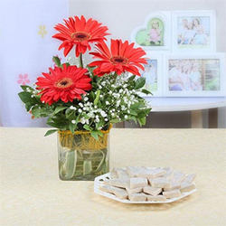 Take a look at this enigmatic combo of red gerberas and a pack of kaju katli that is a wonderful way to express love for your special
