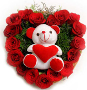 Heart shape arrangement of 20 Red Roses and 6 inch cute soft toy with lots of green fillers. <br>