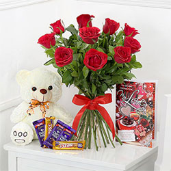 10 red roses, two bars of Cadbury Dairy Milk Chocolate, two bars of 5 Star Chocolate, a greeting card, and a small white teddy