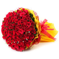 Beautiful 100 red roses bouquet tied with yellow cellophane paper and red ribbon bow.