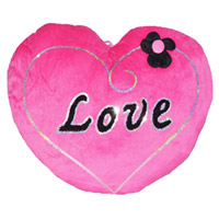 A pink colored heart shaped pillow.