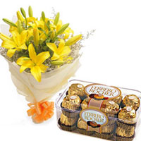 Round Bunch of 6 Yellow Asiatic Lilies in a white paper packing with orange ribbon bow & lot of white fillers 16 pcsFerrero Rocher Chocolate