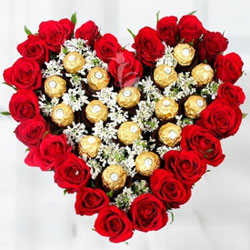 25 fresh Red Roses with seasonal-fillers in a heart-shaped arrangement along-with 16 Ferrero Rocher chocolates in the center of the arrangement.