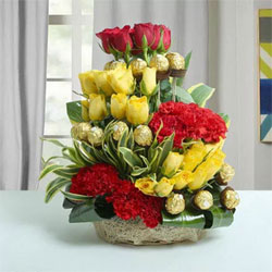 Arrangement of Ferrero Rocher Chocolates - 16 pcs., 12-Red Roses - 15-Yellow Roses -  6-Red Carnations Draceane Leaves & Dry Sticks